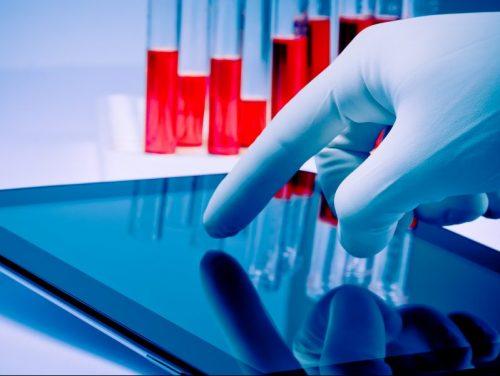 mão na luva médica azul tocando tablet digital em laboratório
